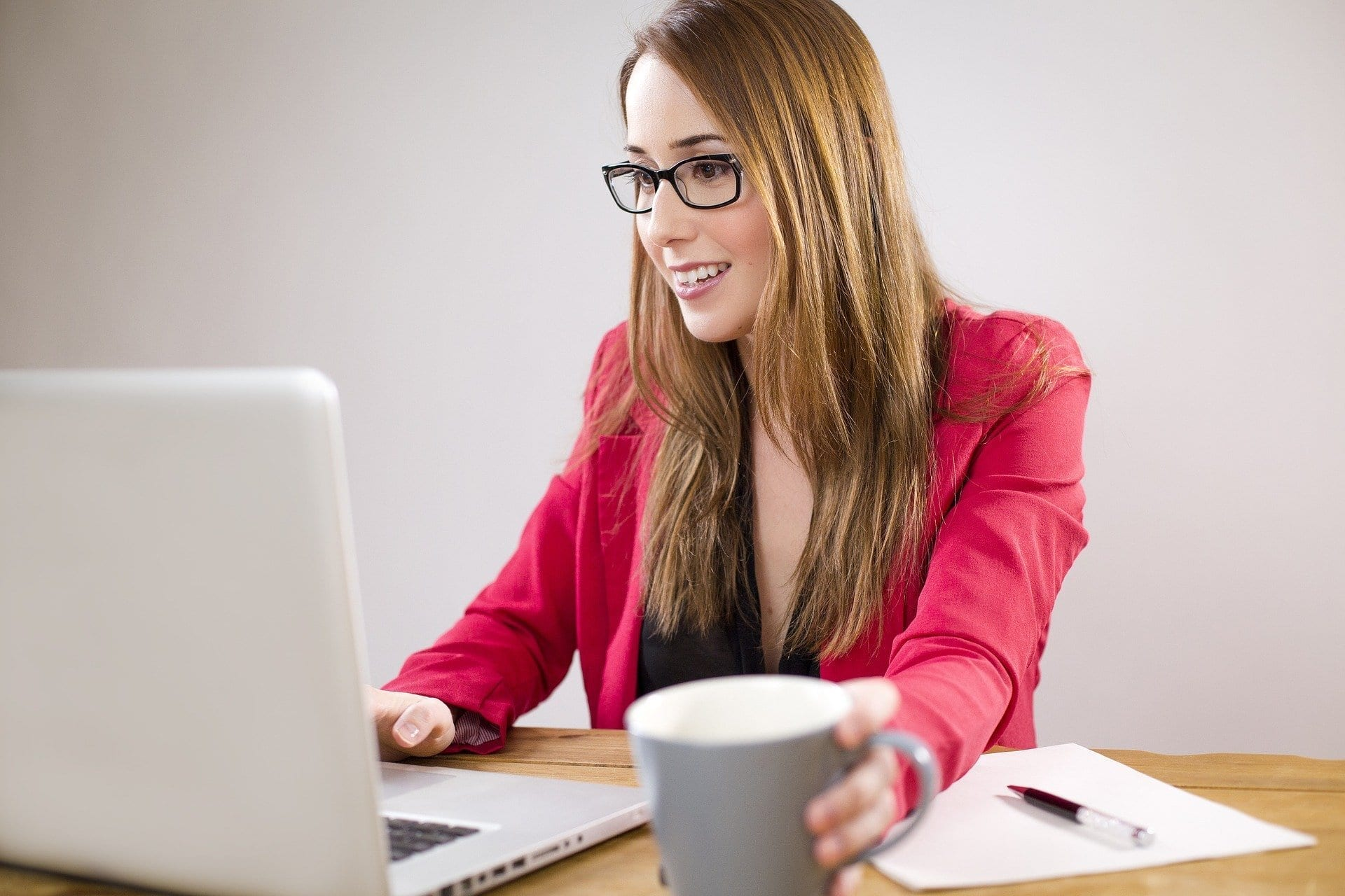 business person wearing pink working at laptop