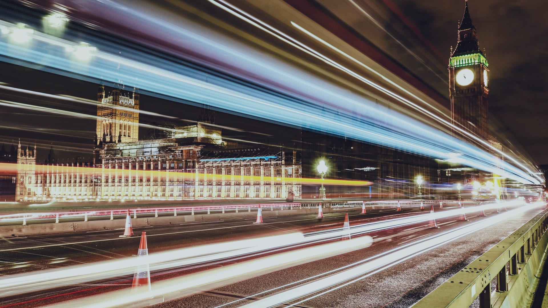 long exposure image showing trail of lights coming from traffic crossing bridge towards Big Ben