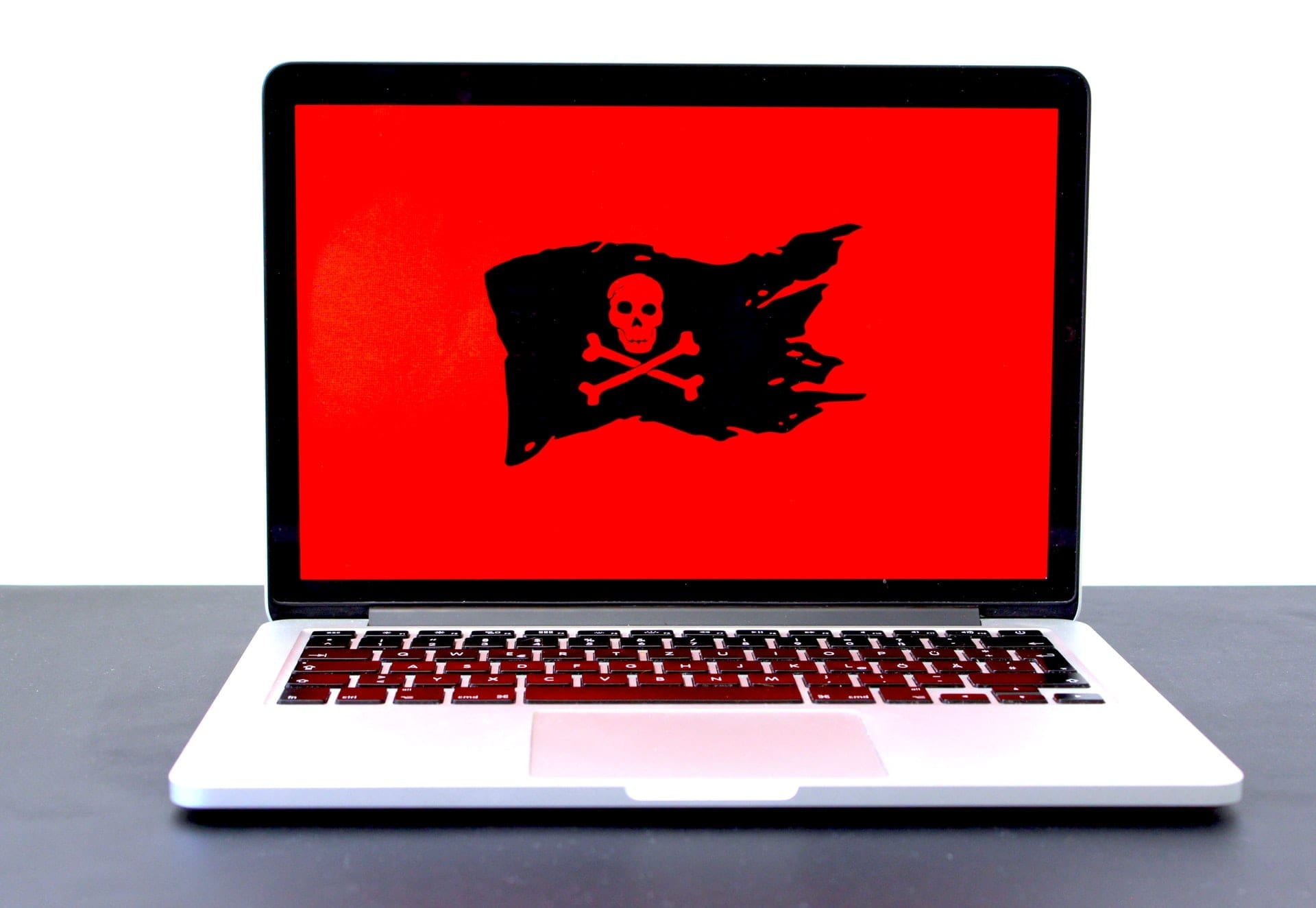 Laptop showing large pirate flag on red background representing malware