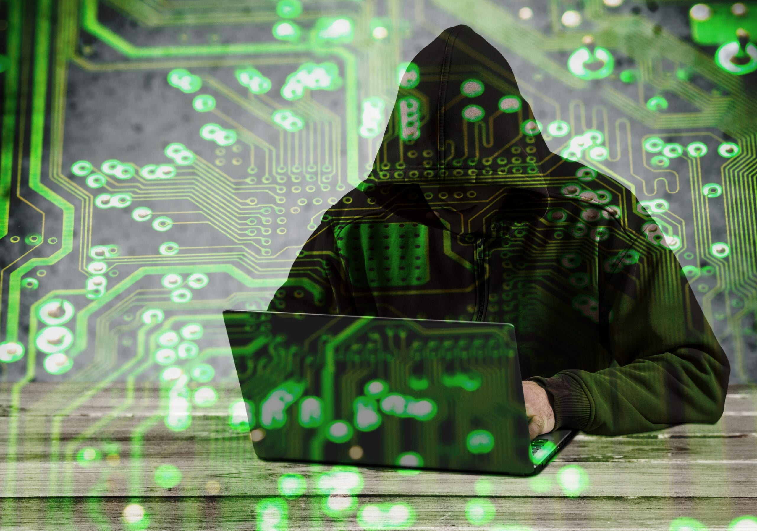 Graphic of a hacker with ahoodie hunched over a laptop